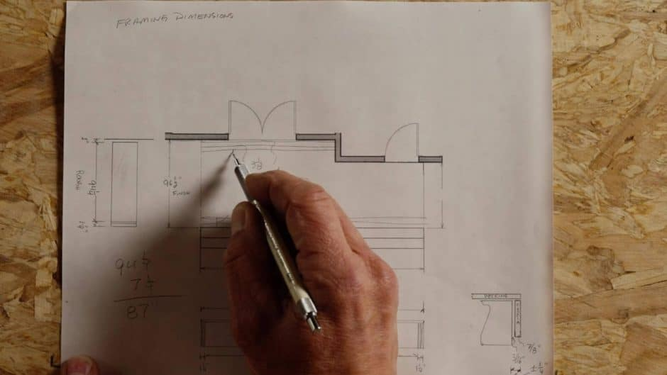 Close-up of a hand drawing on site plans with a pencil