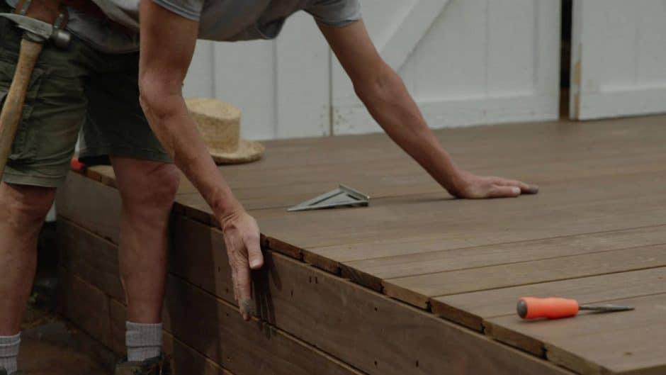 Close-up of worker handling deck boards