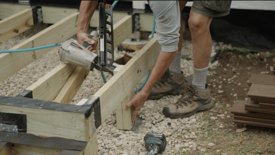 Contractor holds nail gun to beam post on outside deck