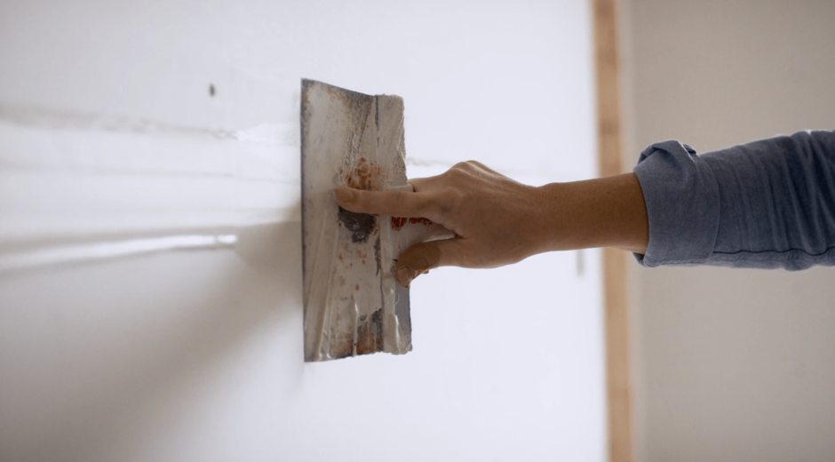 Close-up of hand moving drywall hawk across wall
