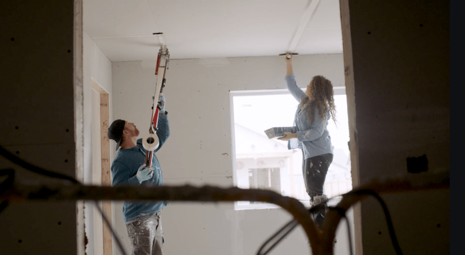 Two contractors mudding and taping a drywall ceiling