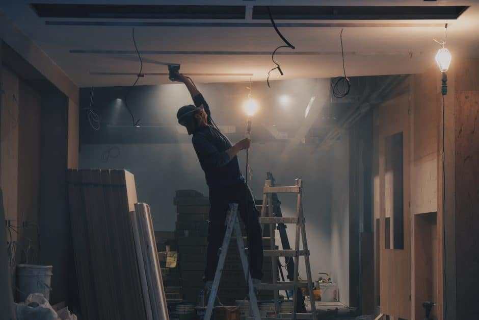 Worker on a ladder reaching towards the ceiling